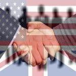 Handschlag vor der Kulisse der britischen und US-amerikanischen Flagge