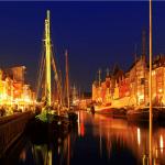 Auf dem Bild ist das Hafenbecken Nyhavn in der dänischen Hauptstadt Kopenhagen zu sehen. Das Foto ist bei Nacht aufgenommen und die alten Straßenlaternen beleuchten die Segelschiffe, bunten Fassaden in den Straßen.