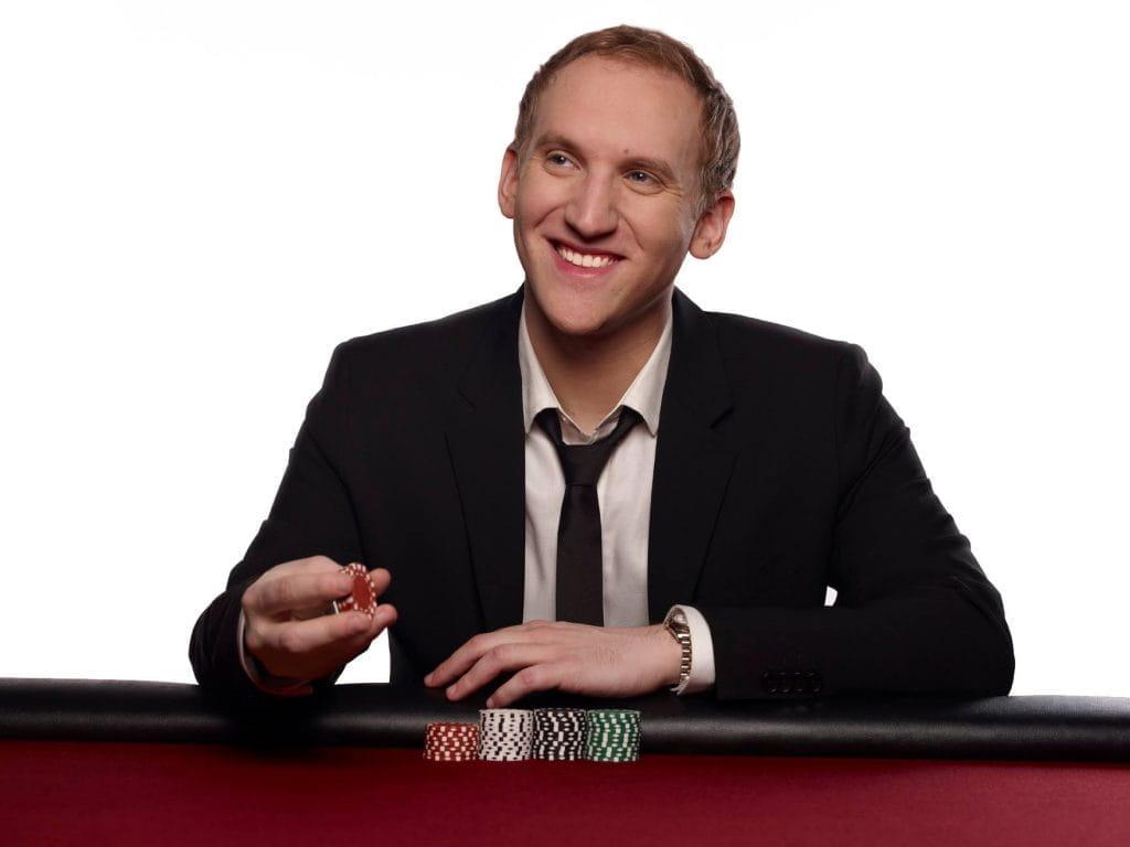 Jason Somerville im Anzug sitzend an einem Pokertisch.