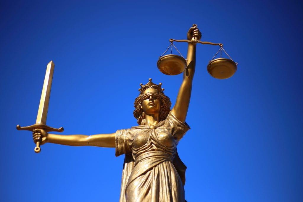 Das Bild zeigt eine Statue von Justitia, der Göttin des Glücks. In der einen Hand hält die Statue ein Schwert, in der anderen Hand eine Waage.