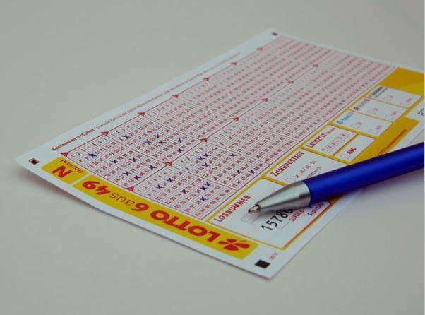 Ein ausgefüllter Lottoschein mit Stift auf einem Tisch.