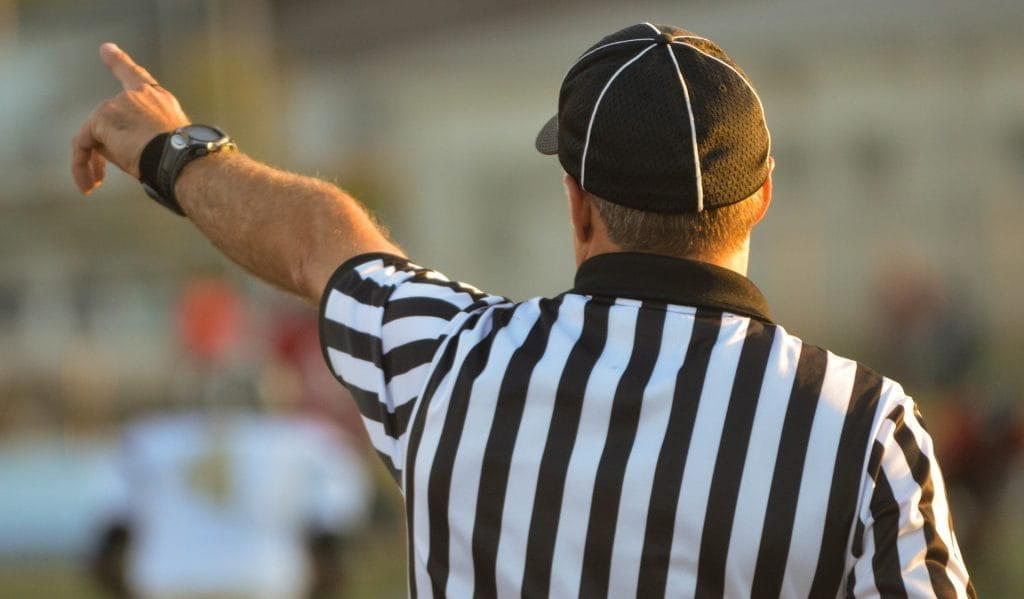 Auf dem Bild ist ein Schiedsrichter im schwarz-weiß gestreiften Tritot mit erhobenem Arm zu sehen.