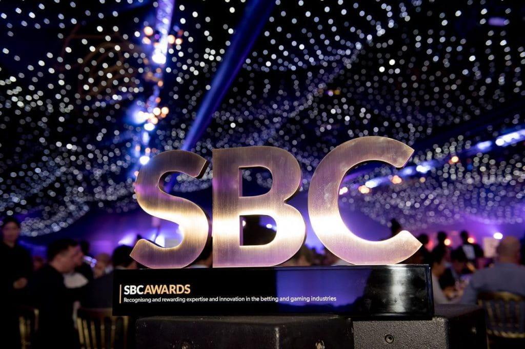 Zu sehen ist die Trophäe des SBC Preises von 2018. Die Trophäe besteht aus den vergoldeten Buchstaben S B und C die auf einem schwarzen Sockel montiert sind.
