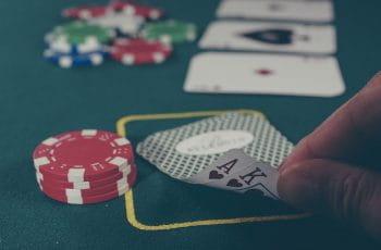 Spielkarten und Spielchips auf einem Poker-Tisch.