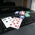 Ein Laptop mit zwei Spielkarten und mehreren Pokerchips.