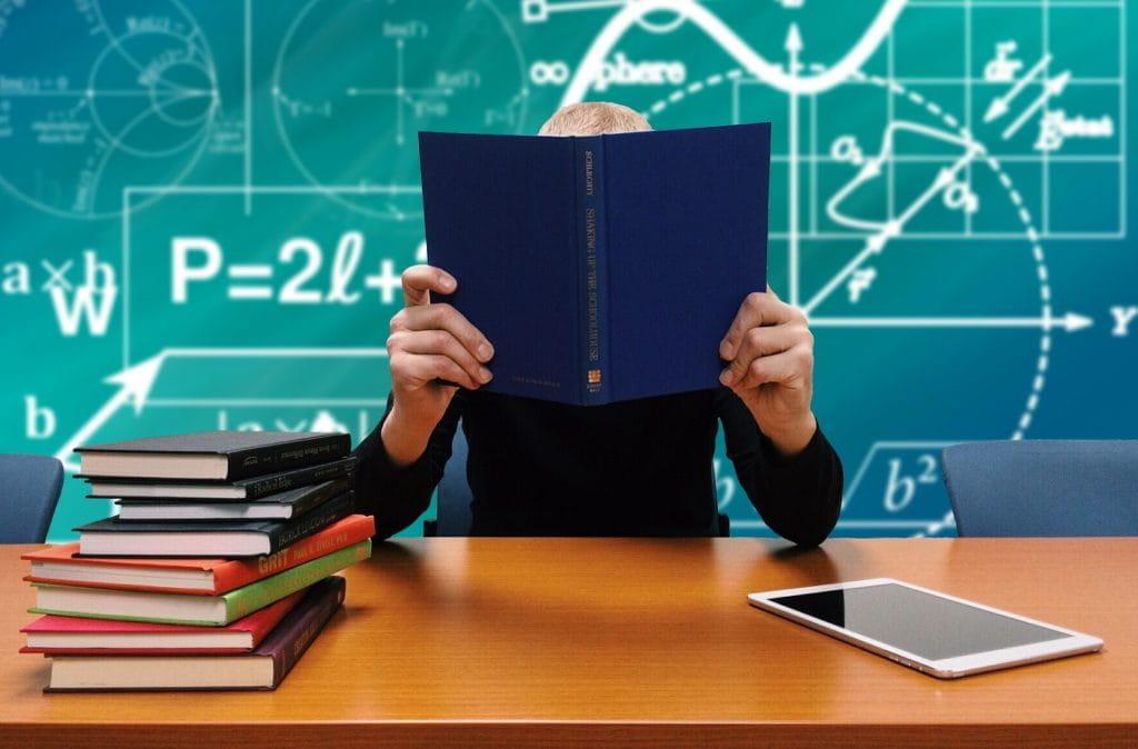 Student vergräbt sich hinter einem Buch; dahinter Formeln.