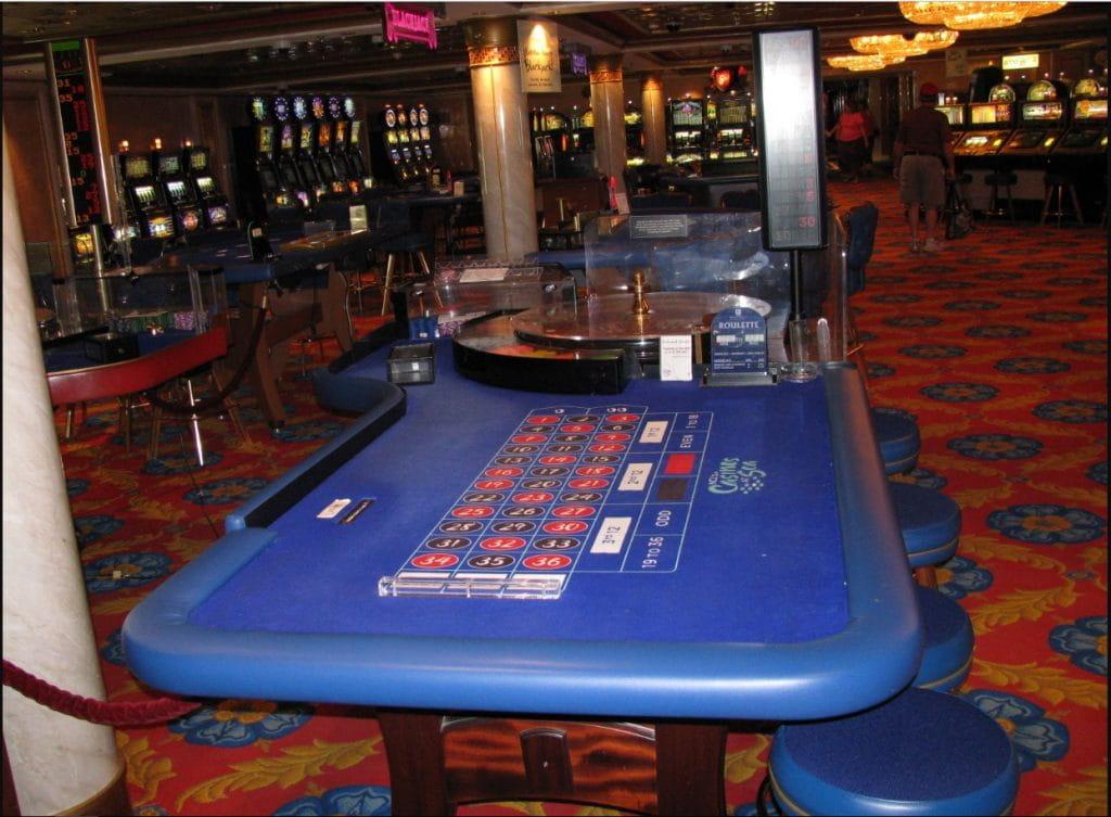 """Blick auf den Roulettetisch des Bordcasinos des Kreuzfahrtschiffes """"Norwegian Dawn"""", im Hintergrund weitere Spieltische und Spielautomaten."""