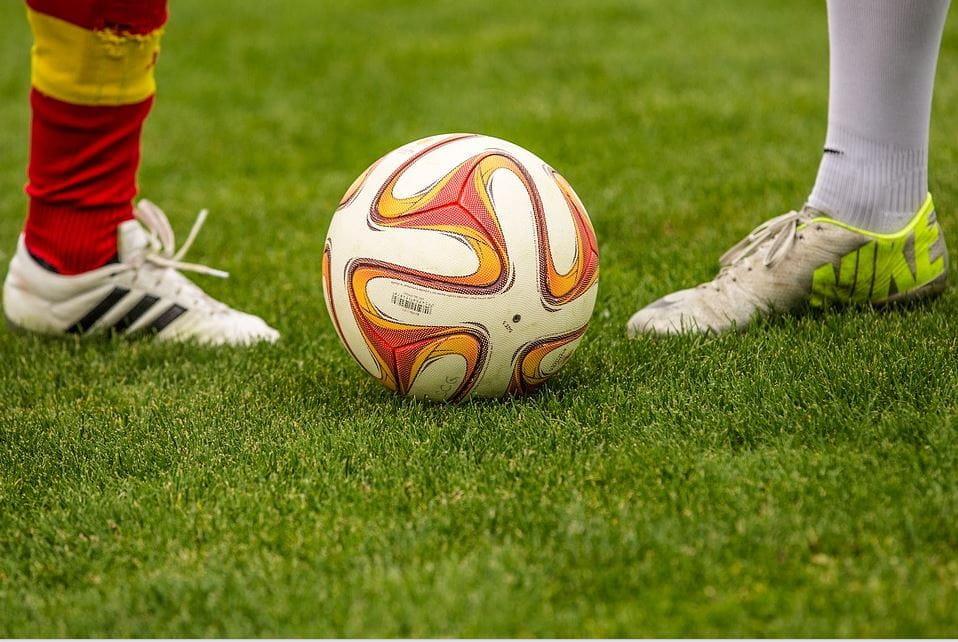 Ein Fussball auf dem Spielfeld und zwei Beine, die sich gegenüberstehen.