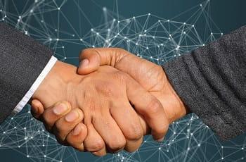 Ein Handshake besiegelt die Fusion.