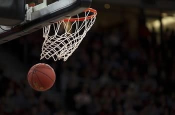 Ein Basketball fliegt durch einen Korb.