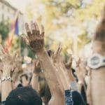 Demonstranten erheben ihre Hände.