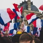 Französische Flaggen werden geschwenkt.