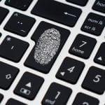 Fingerabdruck auf Enter-Taste einer Tastatur in schwarz-weißer Optik.