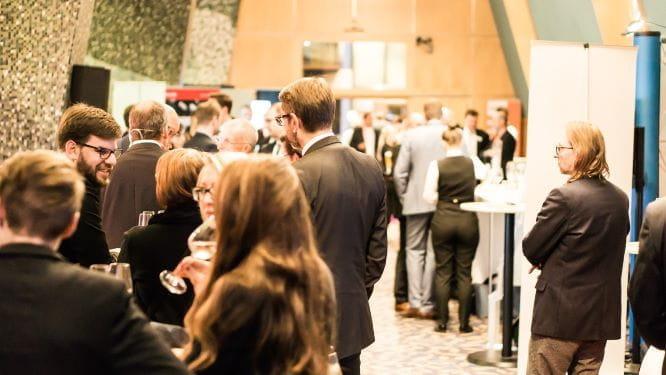 Verschiedene Gesprächsrunden verschiedener Menschen auf einer Konferenz.