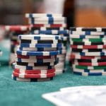 Verschiedene Pokerchips neben Spielkarten auf einem Tisch.