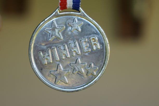 "Silberne Medaille mit ""Winner""-Aufschrift an rot-weiß-blauem Band."