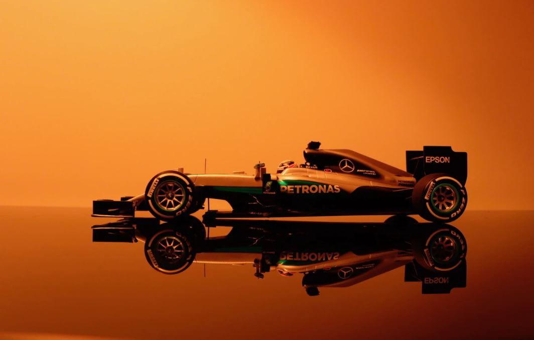 Ein Formel 1 Auto von Mercedes Benz in einem orangenen Showroom. Der Bolide spiegelt sich im Boden wieder.