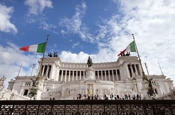 Italienische Flaggen vor einem römischen Monument.
