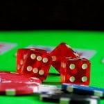 Spielwürfel, Pokerchips und Karten auf einem Casinotisch.