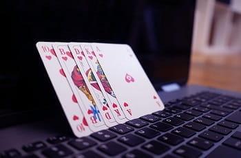 Spielkarten lehnen auf den Armaturen eines Notebooks.
