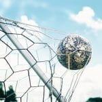 Ein Fußball fliegt ins Netz eine Tores.