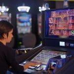 Frau an einem Spielautomaten in einer Spielhalle.