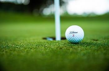 Ein Golfball vor einem Loch.