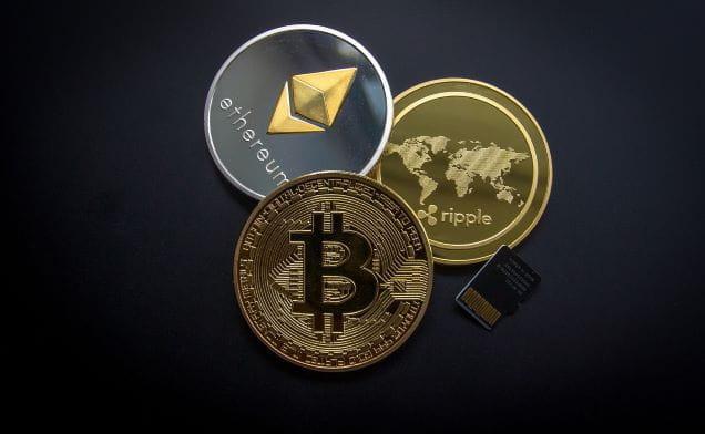 Münzen der Kryptowährungen Bitcoin, Ripple und Ethereum.