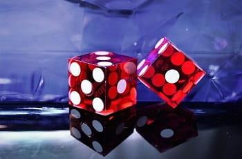 Zwei rote Casino-Spielwürfel auf einer Tischfläche.