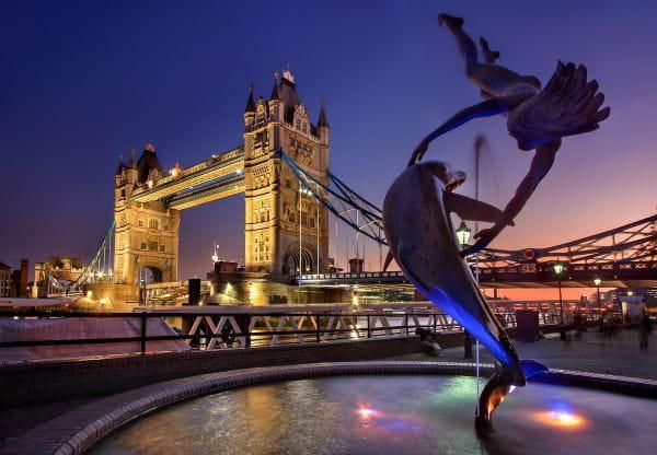 Tower Bridge in London bei Nacht in goldenem Licht teilweise beleuchtet.