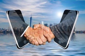 Ein digitaler Handschlag vor eine Städteskyline.