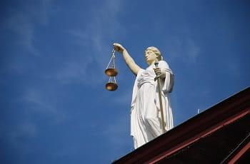 Eine Staue der Justitia auf einem Gebäude.