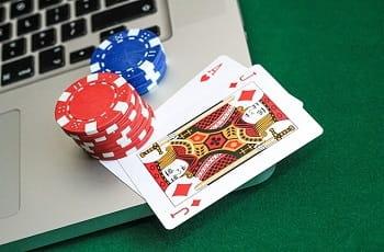 Spielkarten und Pokerchips auf einer Laptoptastatur.