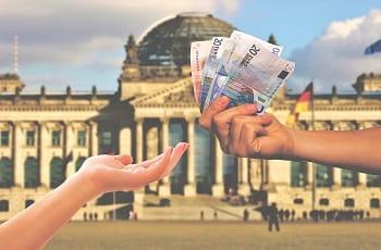 Geldscheine werden vor dem Berliner Bundestag überreicht.