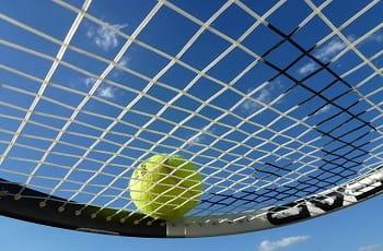 Ein Tennisball auf dem Netz eines Tennisschlägers.