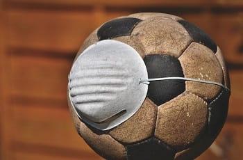 Ein Fußball trägt eine Atemschutzmaske.