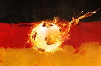 Ein brennender Fußball vor einer deutschen Flagge.
