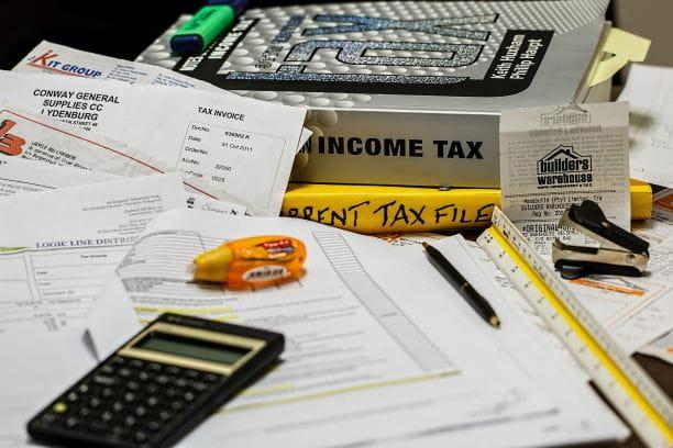 Dokumente, Bücher und Taschenrechner auf einem Tisch.