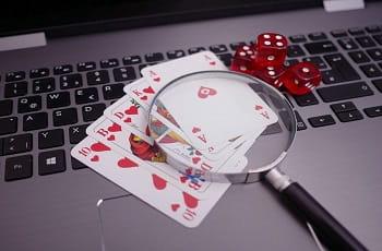 Spielkarten, Würfel und Lupe auf einem Laptop.