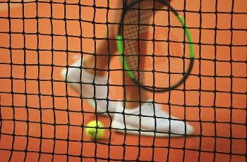 Eine Tennisspielerin läuft hinter dem Mittelnetz.