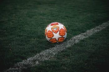 Ein orangeroter Fußball auf dem Rasen.