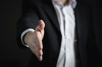 Ein Mann im Jackett reicht seine Hand.