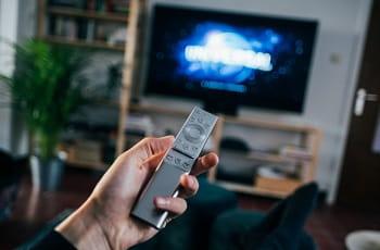 Eine TV-Fernbedienung in der Hand eines Zuschauers.