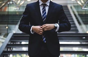 Ein Geschäftsmann knöpft sein Jackett zu.