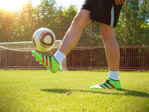 Man hält auf einem Fußballplatz einen Ball hoch.