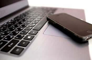 Ein Smartphone liegt auf einer Laptoptastatur.