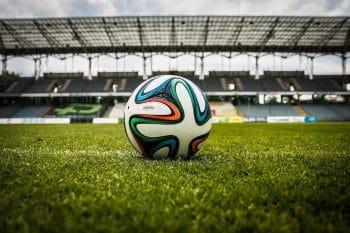 Ein Fußball auf Rasen in einem Fußballstadion.