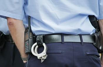 Handschellen, Dienstwaffe und Funkgerät am Gürtel eines Polizisten.