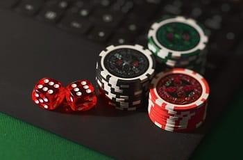 Würfel und Pokerchips auf einer Laptoptastatur.