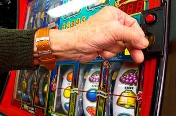 Ein Mensch vor einem Spielautomaten in einem Casino.